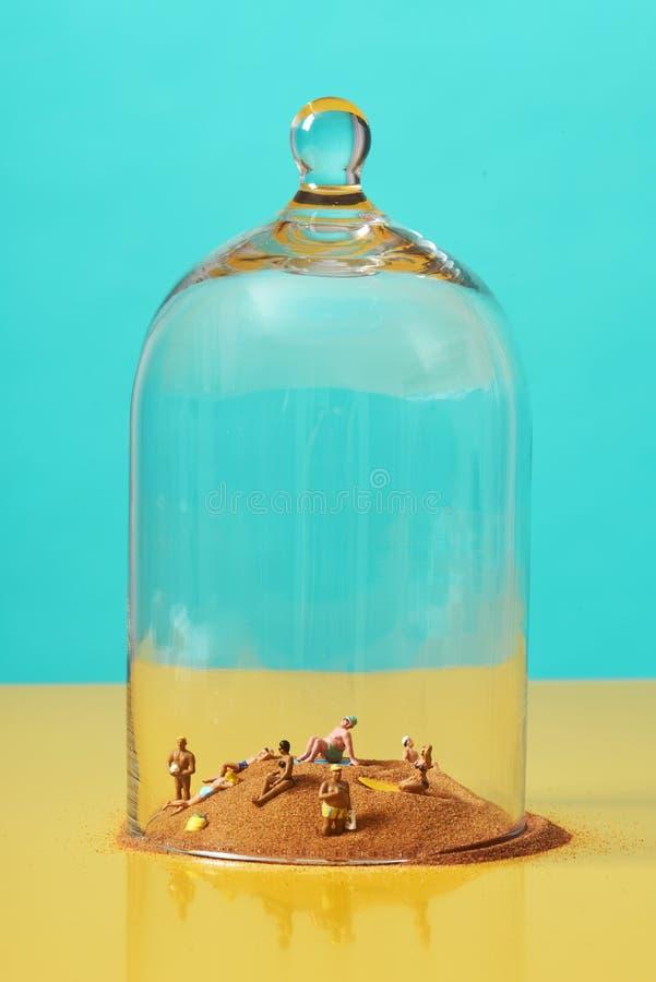 沙子上的微型人,钟罩里 免版税库存图片