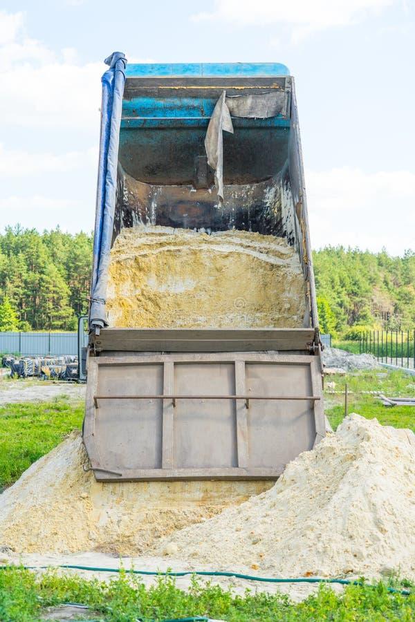 沙子交付建筑的 翻斗车卸载沙子 您的文本的地方 免版税图库摄影