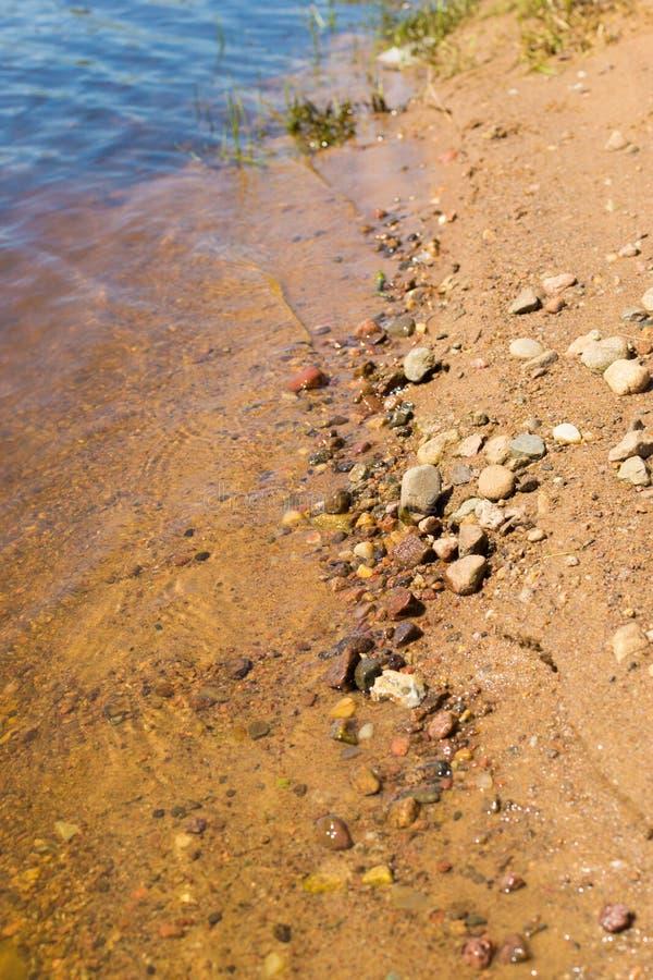 沙子和石头在河水在海滩 免版税库存图片