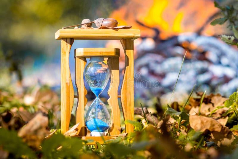 沙子在干燥叶子中的森林里计时在火的背景在autumn_的 免版税库存图片