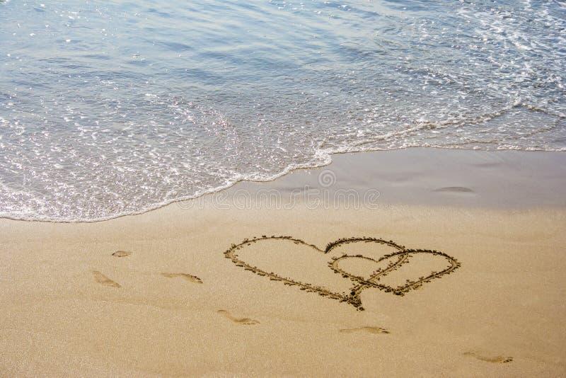 沙子在海滩的心脏夫妇 免版税库存图片