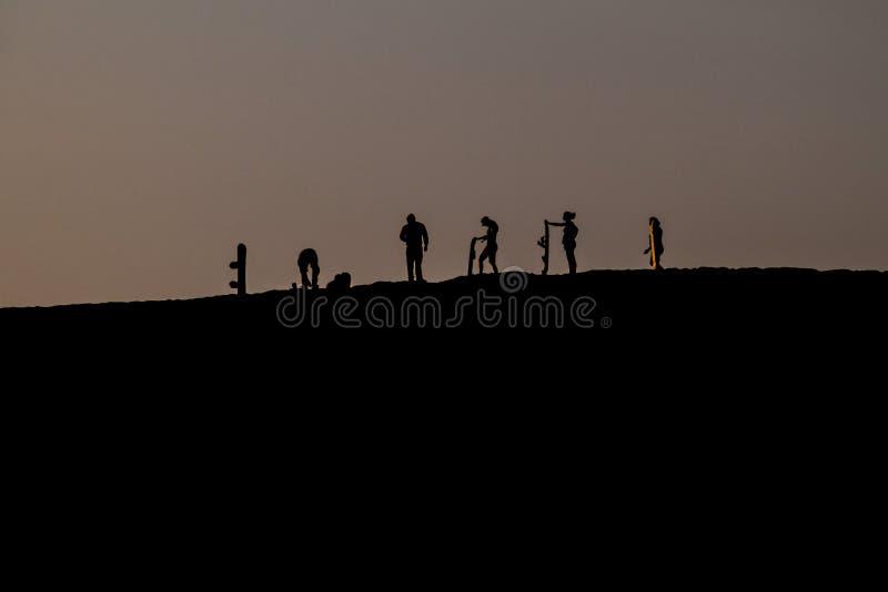 沙子房客剪影在日落期间的在Ica,Pe附近的沙漠绿洲Huacachina附近 免版税库存图片