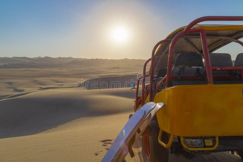 沙子搭乘,在沙漠停放的沙地汽车在日落期间在Ica,秘鲁的Huacachina绿洲 免版税图库摄影