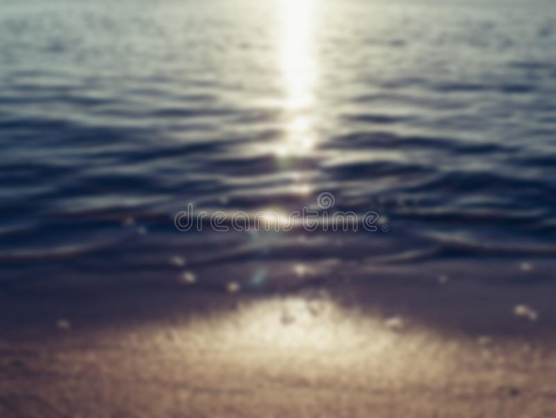 沙子海滩和海在日落光,被弄脏的抽象夏天背景挥动 免版税图库摄影