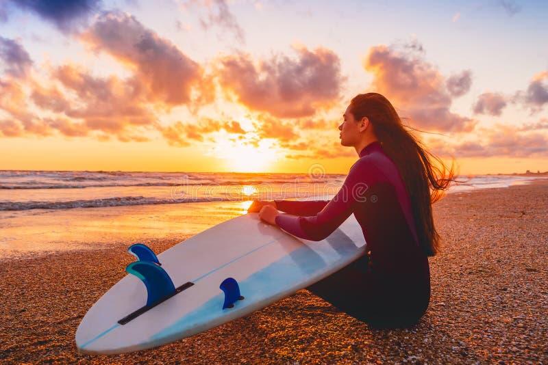 沙子海滩的冲浪者女孩与在温暖的日落或日出的冲浪板 免版税库存照片
