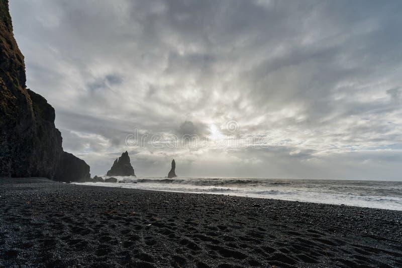 黑沙子海滩Reynisfjara在冰岛 岩石在水中 重点前景海浪通知 有风 多云天空 免版税图库摄影