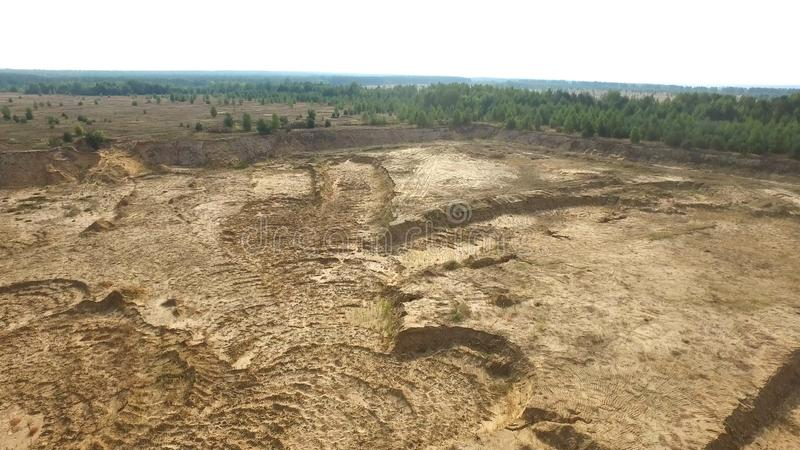 沙子猎物在乡下 场面 空的黄色猎物顶视图与路和坑的在绿叶背景和 免版税图库摄影