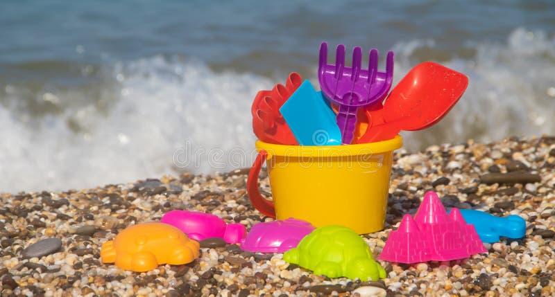 沙子的塑料儿童的玩具在海的背景 r 塑料沙子玩具 明亮的玩具 沙子建筑 图库摄影