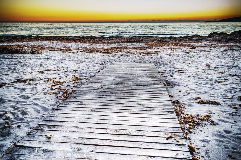 沙子的木木板走道在日落 图库摄影