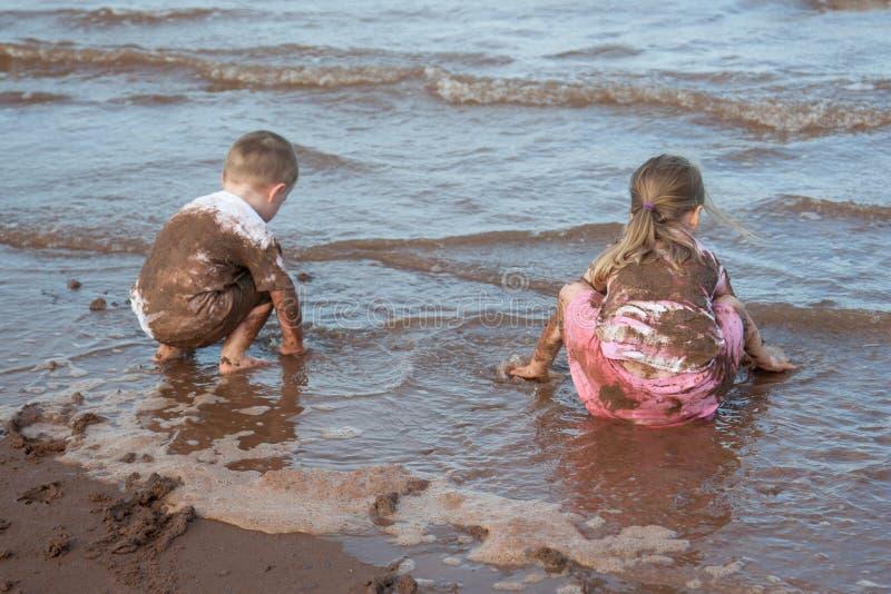沙子盖了使用在海的孩子 免版税库存图片