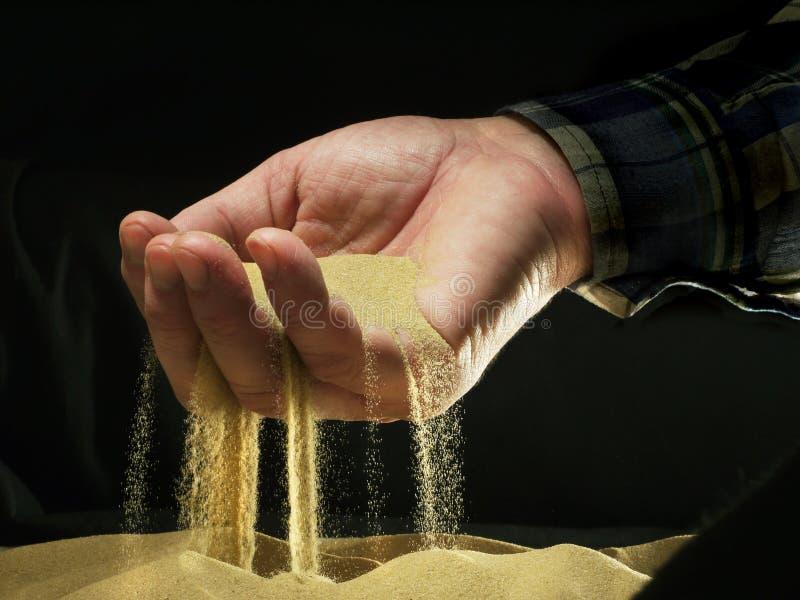 沙子通过手指 图库摄影