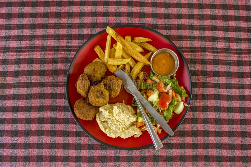 沙拉三明治、土豆、hummus、沙拉、调味汁和叉子与一把刀子在一块红色板材在一张方格的红色白色黑桌布顶视图 免版税库存照片