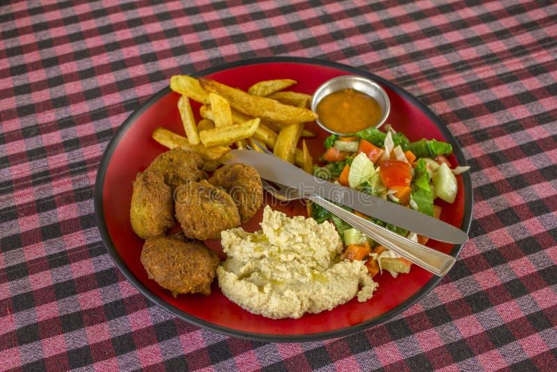 沙拉三明治、土豆、hummus、沙拉、调味汁和叉子与一把刀子在一块红色板材在一张被弄脏的方格的红色白色黑桌布 库存图片