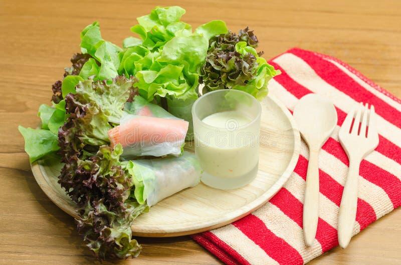 沙拉卷菜和螃蟹忠心于在木头的色拉调味品 库存图片