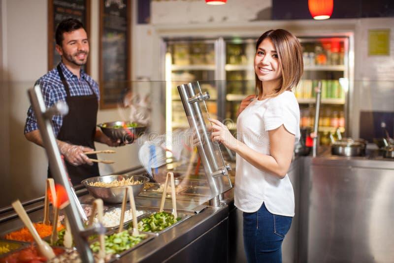 沙拉柜台的逗人喜爱的西班牙妇女 免版税库存照片