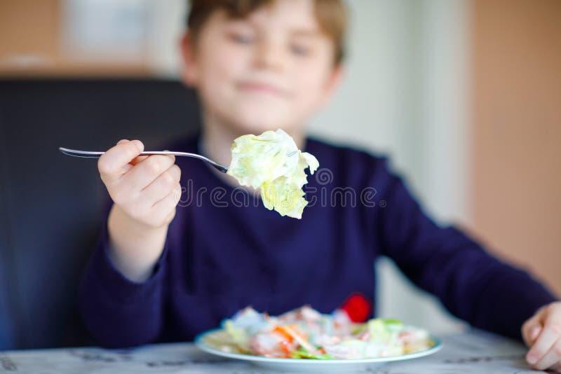 沙拉特写镜头在举行由愉快的孩子男孩的叉子的吃用不同的菜的新鲜的沙拉作为膳食或快餐 ?? 库存图片