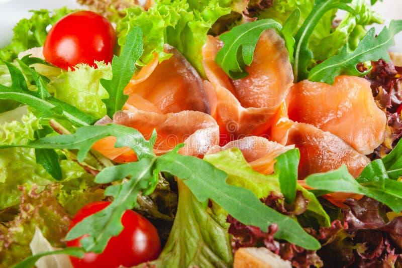 沙拉用三文鱼,西红柿、油煎方型小面包片和莴苣在白色板材 免版税库存照片
