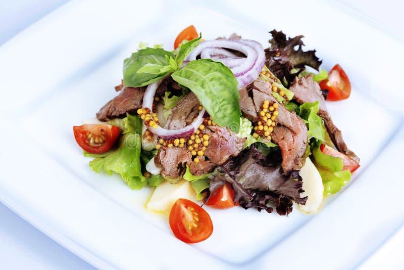 沙拉用煮沸的猪肉,西红柿,芥末 免版税库存图片