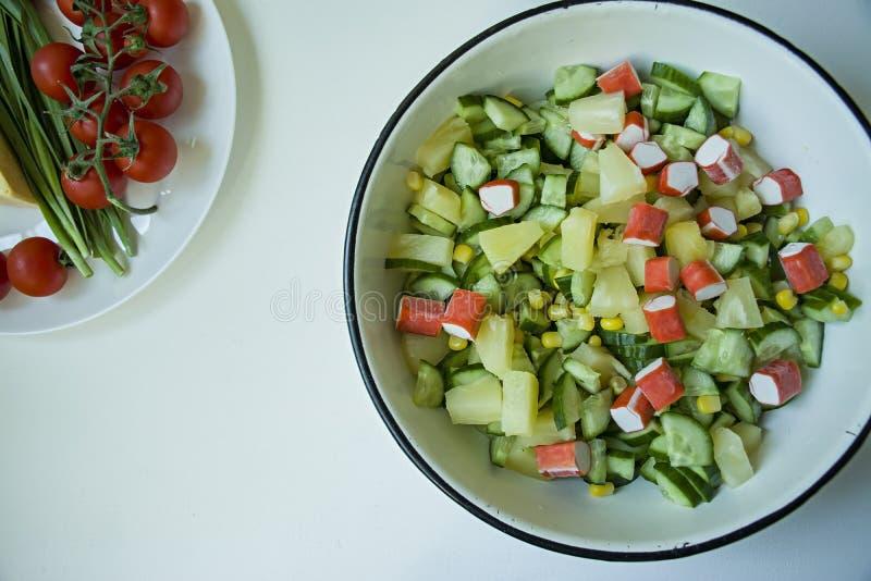 沙拉用玉米,螃蟹棍子,在一个白色碗的黄瓜在白色背景 素食沙拉 E 免版税库存图片