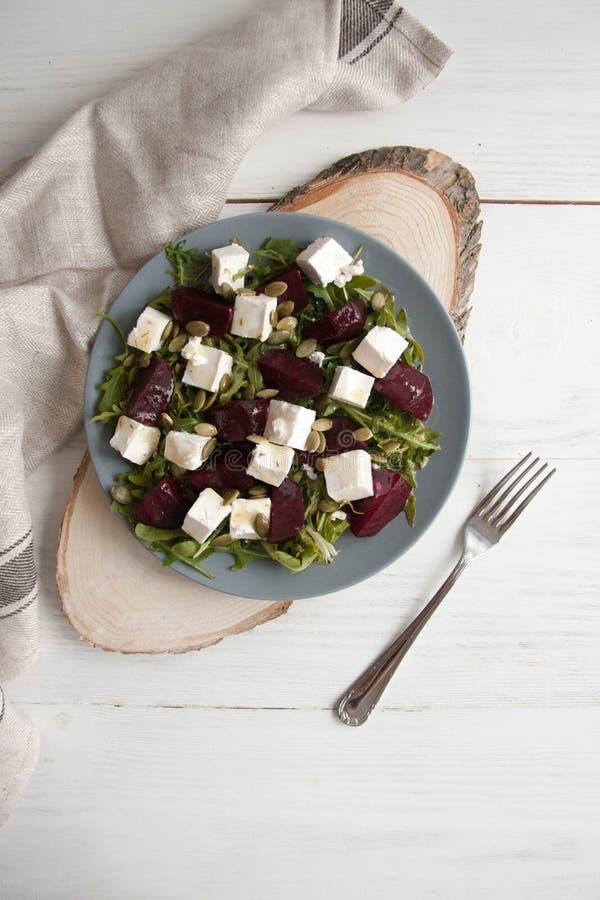 沙拉用甜菜、希腊白软干酪和南瓜籽在一块灰色板材 免版税库存照片
