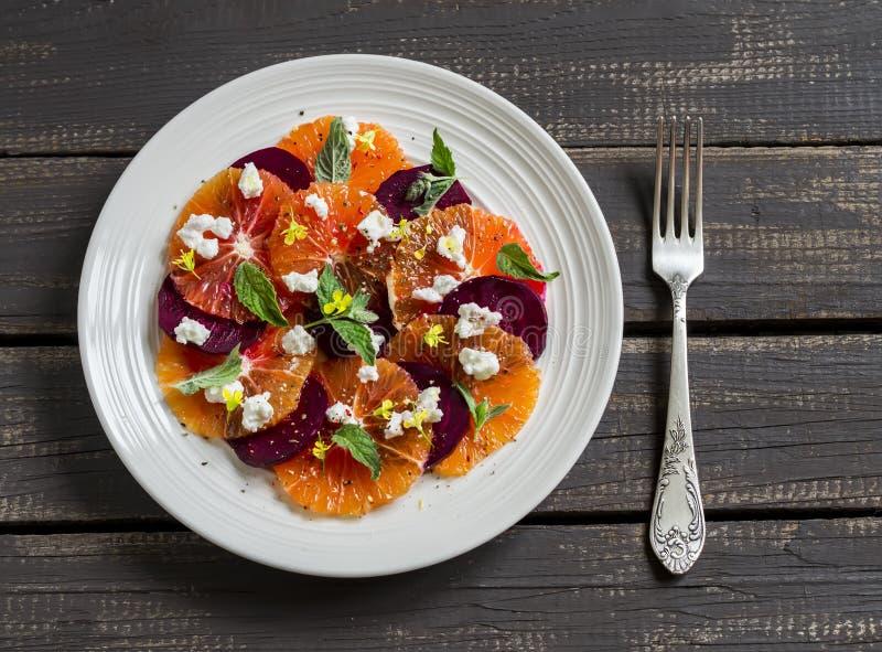 沙拉用甜菜、桔子和软干酪在一块白色板材 免版税库存图片