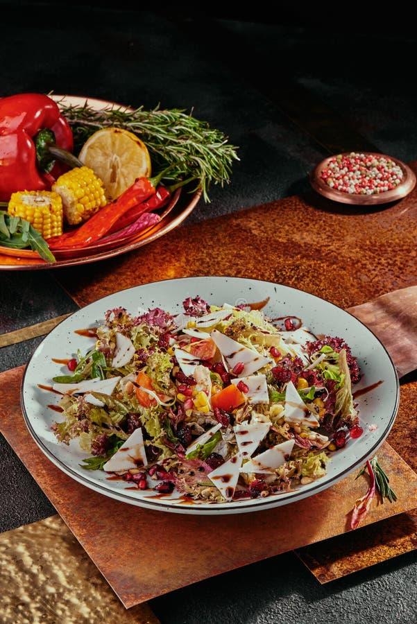 沙拉用石榴、玉米、蕃茄、芝麻菜、帕尔马干酪和蔓越桔在一块白色板材在铜背景 图库摄影