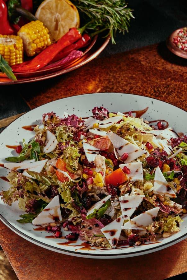 沙拉用石榴、玉米、蕃茄、芝麻菜、帕尔马干酪和蔓越桔在一块白色板材在铜背景 库存照片