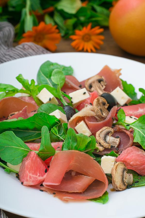 沙拉用菠菜、乳酪、火腿、葡萄柚和芳香抚人的调味汁在木农村背景 顶视图 特写镜头 库存图片