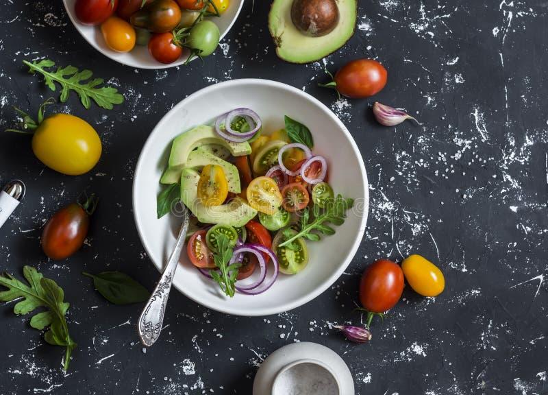 沙拉用蕃茄和鲕梨在黑暗的背景 库存图片