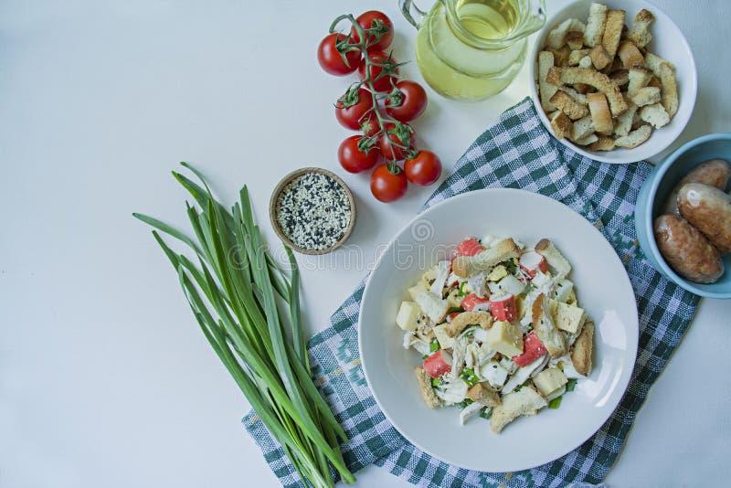 沙拉用薄脆饼干、螃蟹棍子、鸡内圆角、新鲜的用橄榄油晒干的草本和不幸在一块白色板材服务 库存图片