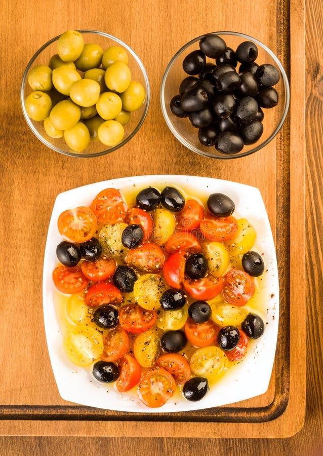 沙拉用西红柿和橄榄在木 免版税库存照片