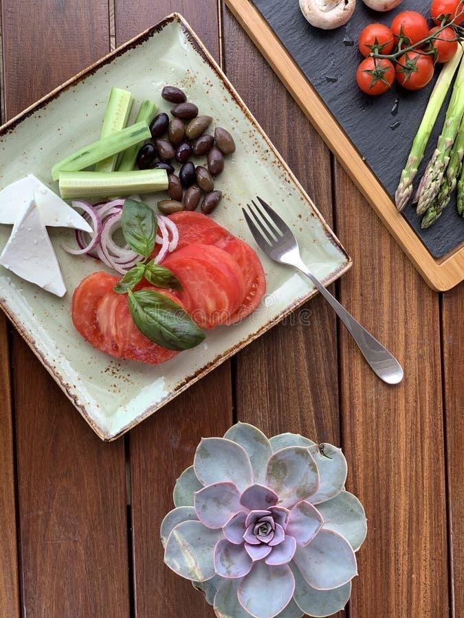 沙拉的顶上的特写镜头射击用豆和乳酪在一块方形的板材有叉子的 免版税图库摄影