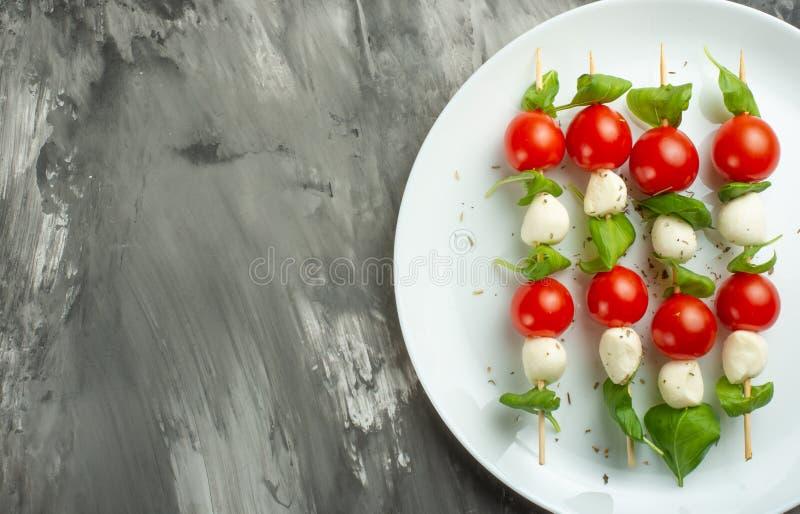 沙拉Caprese -烤肉串用蕃茄、无盐干酪和蓬蒿、意大利烹调和一健康素食在黑暗的背景 库存照片