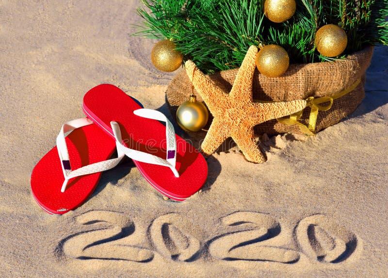 沙滩上的2020年新年 沙滩上的圣诞树,上面有圣诞球、拖鞋和海星 免版税图库摄影