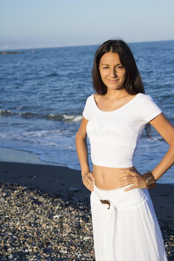 沙滩上穿着白裙的漂亮女人 库存照片