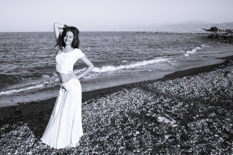 沙滩上穿着白裙的漂亮女人 免版税库存图片