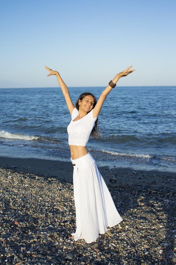 沙滩上穿着白裙的漂亮女人 库存图片