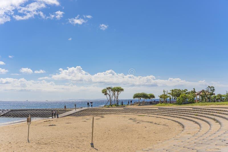 沙滩伞和棕榈树在日落海滩在北谷町市在冲绳岛美国村庄在日本 免版税库存图片