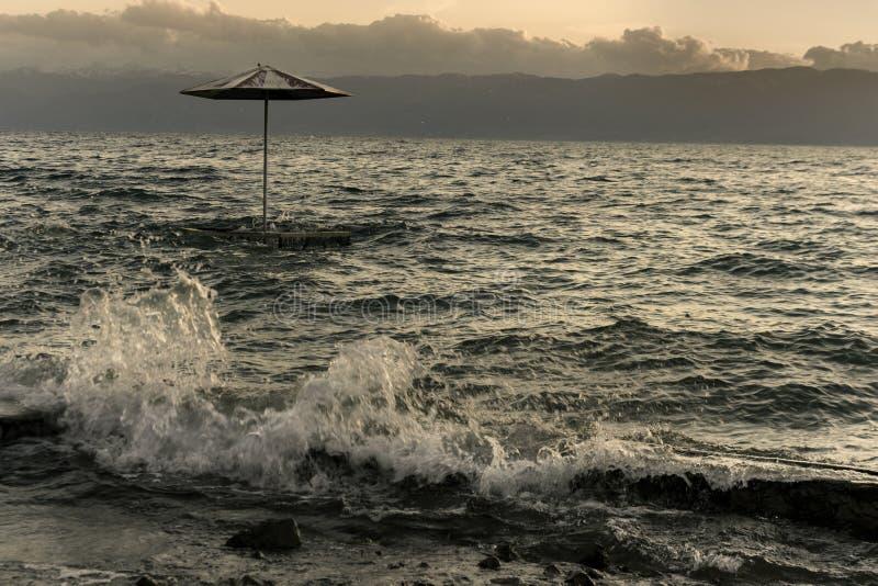 沙滩伞在多暴风雨的天气日落的奥赫里德湖 免版税库存照片