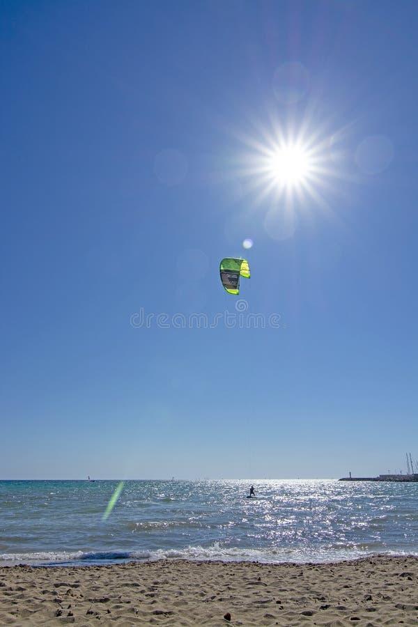 沙滩和kitesurfer飞行高反对与星状太阳和火光的天空蔚蓝 库存图片