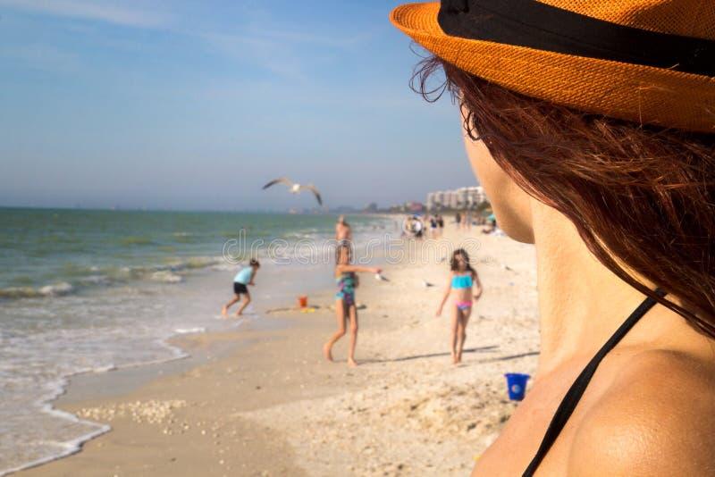 沙滩家庭假日,俏丽的使用在游泳衣的太阳的妇女细节观看的孩子在美丽的海海滩在佛罗里达 免版税图库摄影