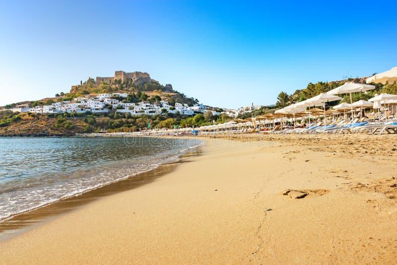 沙滩看法在Lindos,上城海湾的在背景R中 免版税库存图片