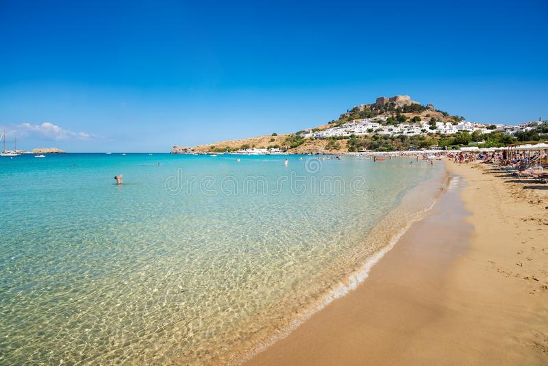 沙滩看法在Lindos,上城海湾的在背景R中 图库摄影
