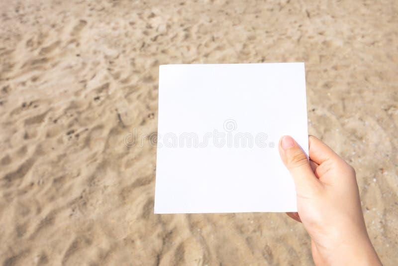 沙滩纹理背景中沙子的女手握白纸 库存照片