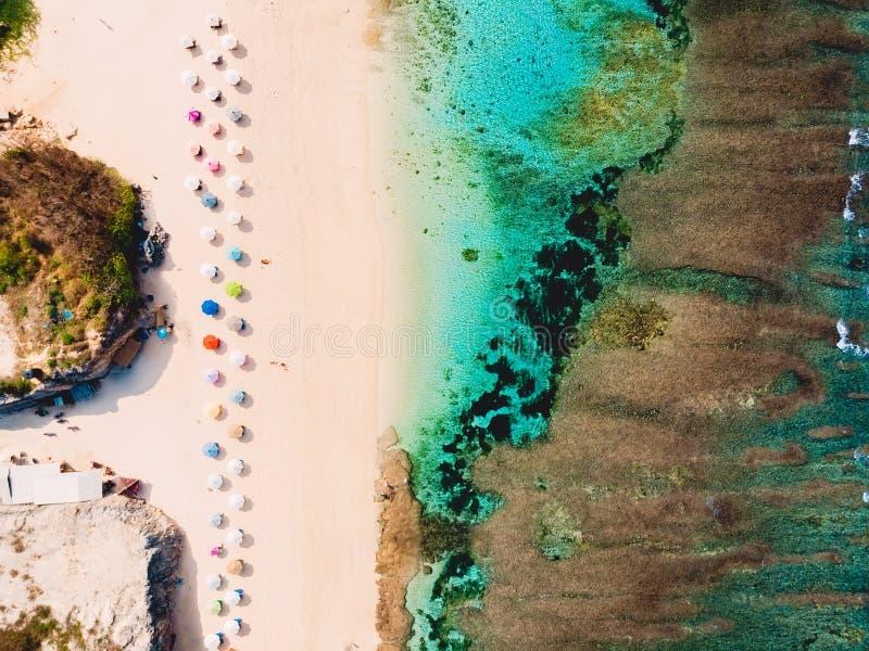 沙滩顶视图与绿松石海洋和明亮的五颜六色的伞,空中射击的 库存图片