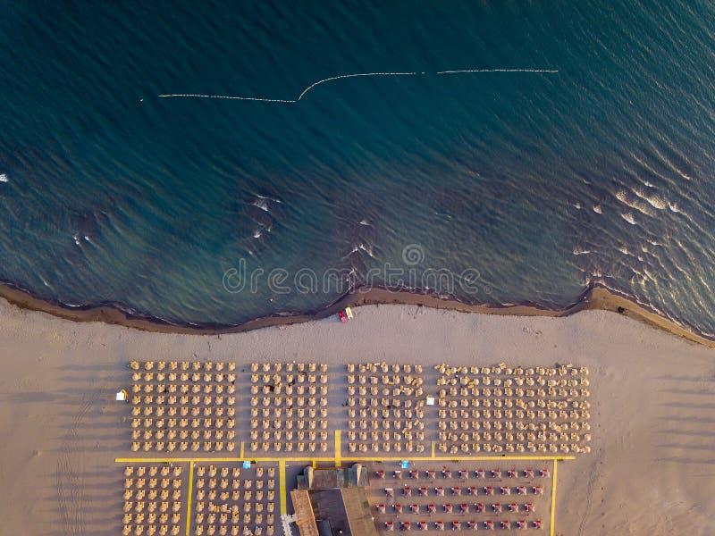 沙滩鸟瞰图与黄色sunbeds和木伞的在日落 库存图片