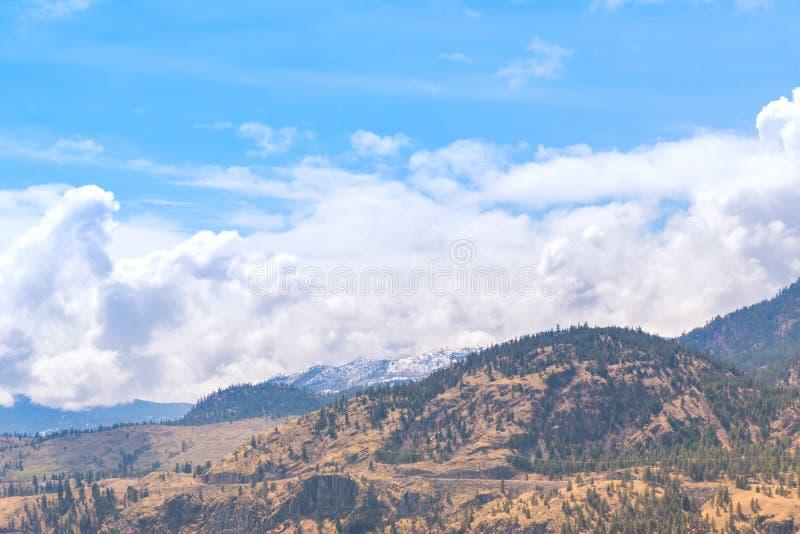 沙漠小山风景与积雪的山在距离和蓝天的与云彩 免版税库存照片
