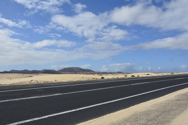 沙漠路山和多云天空 免版税库存照片