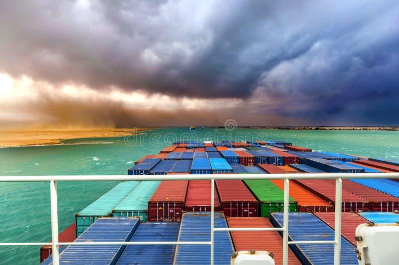 沙漠风暴在苏伊士运河,埃及 在护卫舰的大集装箱船 免版税库存图片