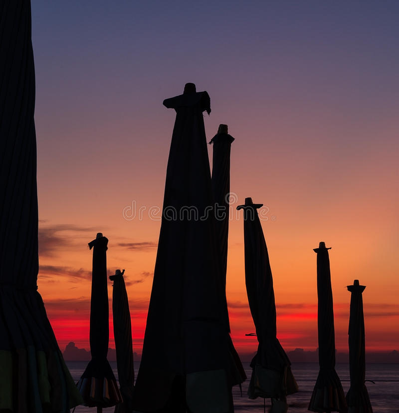 沙滩伞在日落的晚上 图库摄影